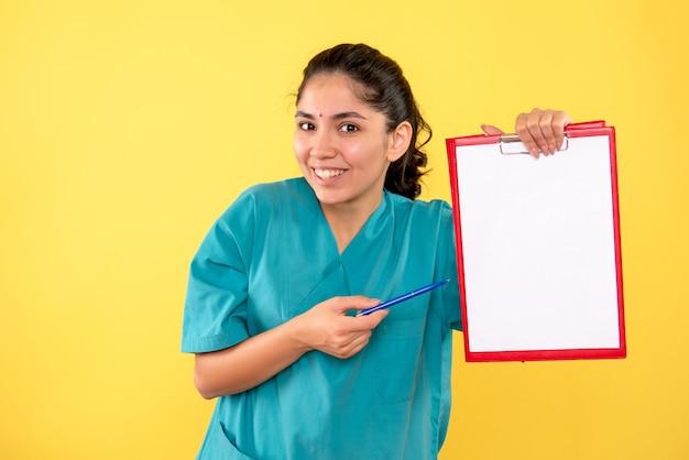 노란색 배경에 클립 보드와 펜을 들고 전면보기 행복 한 젊은 여성