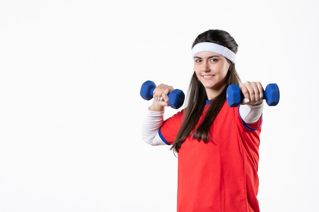 Front view happy young female in sport clothes with blue dumbbells