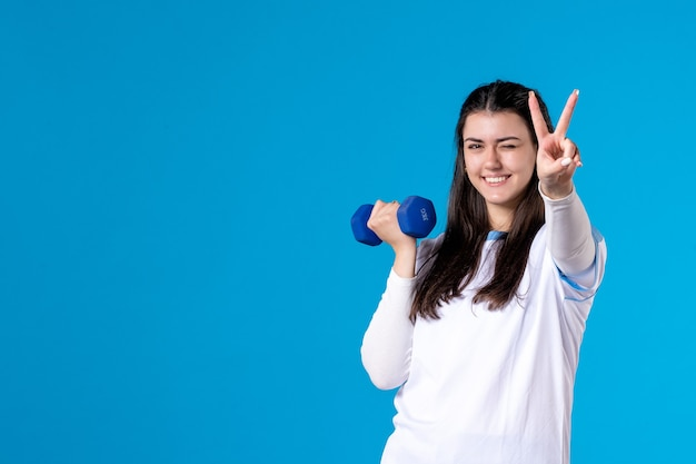 Front view happy young female working out with blue dumbbells on blue