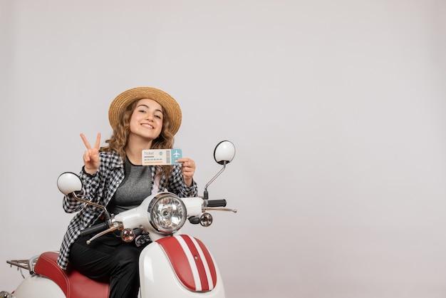 Vista frontale di felice giovane ragazza sul ciclomotore tenendo il biglietto facendo segno di vittoria sul muro grigio