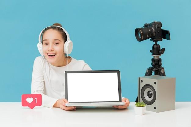 正面のラップトップを提示する幸せな若い女の子