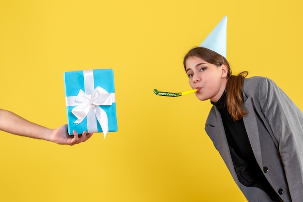 Front view happy young girl with party cap using noisemaker looking at gifbox