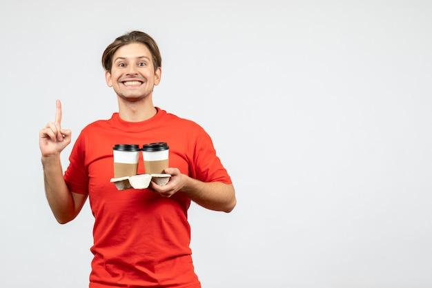 Vista frontale del giovane ragazzo felice in camicetta rossa che tiene il caffè in bicchieri di carta e rivolto verso l'alto su sfondo bianco