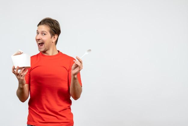 Vista frontale del giovane ragazzo felice in camicetta rossa che tiene scatola di carta e cucchiaio su sfondo bianco
