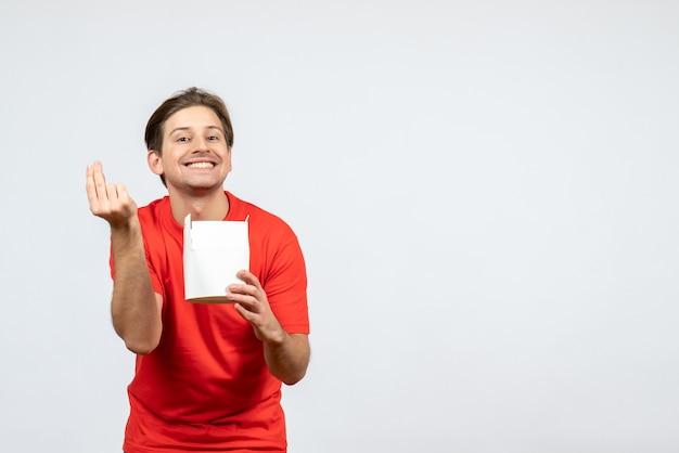 Vista frontale del giovane ragazzo felice in camicetta rossa che tiene la scatola di carta su priorità bassa bianca
