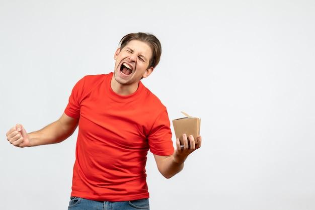 Vista frontale del giovane ragazzo felice in camicetta rossa che tiene piccola scatola su priorità bassa bianca