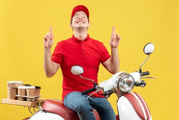 Vista frontale del giovane ragazzo felice che porta la camicetta rossa e il cappello che trasporta gli ordini che indicano su su fondo giallo