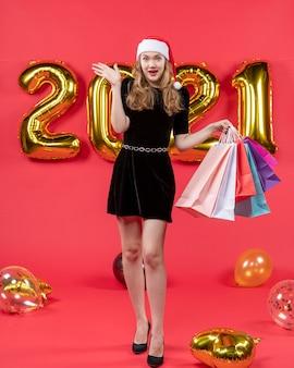 赤のショッピング バッグの風船を保持している黒のドレスで幸せな若い女性の正面図