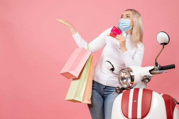 Front view happy young lady with mask holding shopping bags and cards near moped