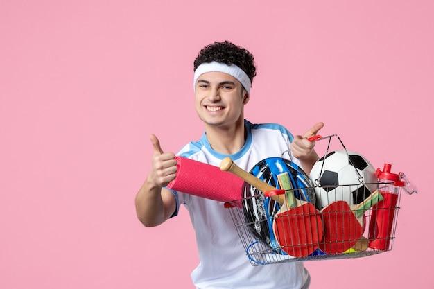スポーツのものでいっぱいのバスケットとスポーツ服を着た幸せな若い男性の正面図