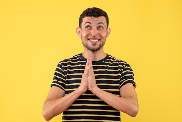 Giovane felice di vista frontale in maglietta a strisce in bianco e nero che unisce le mani insieme su fondo isolato giallo
