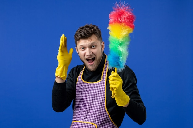 Front view happy young man holding duster on blue space