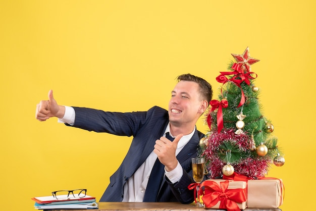 Front view of happy young man making thumb up sign sitting at the table near xmas tree and gifts on yellow