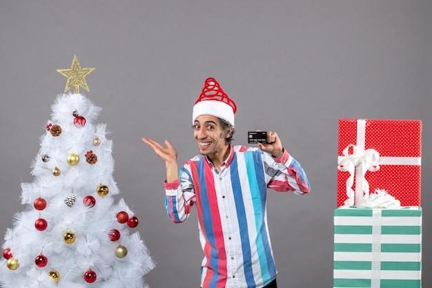 흰색 크리스마스 트리를 보여주는 전면보기 행복 한 젊은 남자 포인트 손가락