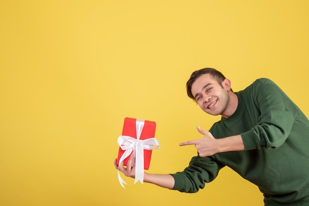 Front view happy young man pointing at gift on yellow