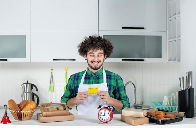 Vista frontale di un giovane felice in piedi dietro il tavolo con vari pasticcini e con in mano una carta di credito nella cucina bianca