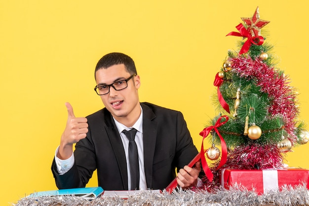 Front view happy young man in a suit sitting at the table making thumb up sign xmas tree and gifts