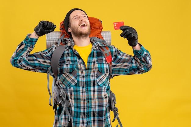 Vista frontale del giovane felice con il viaggiatore con zaino e sacco a pelo che tiene la carta di credito