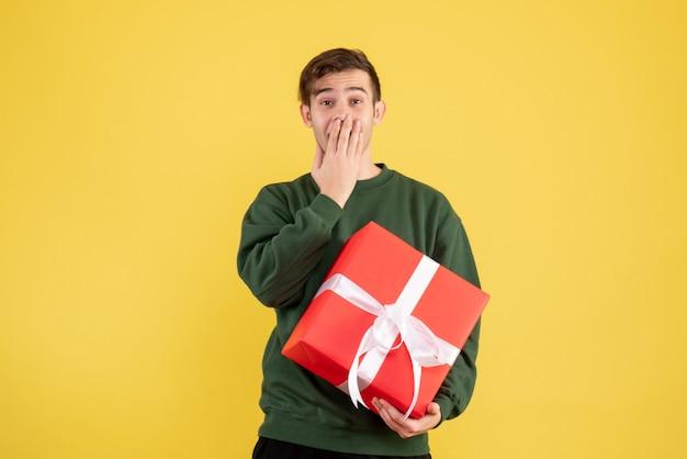Вид спереди счастливый молодой человек с зеленым свитером, стоящий на желтом