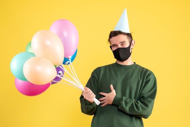 파티 모자와 노란색에 서있는 다채로운 풍선 전면보기 행복 한 젊은 남자