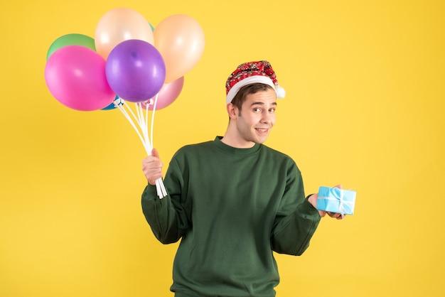 산타 모자와 노란색에 서있는 다채로운 풍선 전면보기 행복 한 젊은 사람