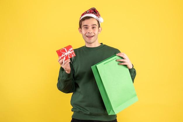 Вид спереди счастливый молодой человек в шляпе санта-клауса, держащий зеленую хозяйственную сумку и подарок, стоящий на желтом