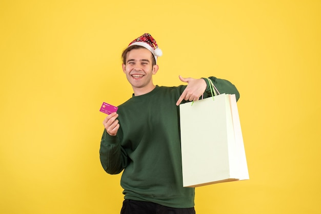 Front view happy young man with shopping bags standing on yellow