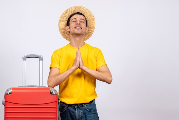 Front view happy young man with yellow t-shirt and suitcase joining hands together