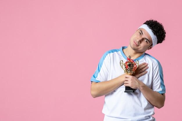 Вид спереди счастливый молодой игрок в спортивной одежде с золотой чашкой