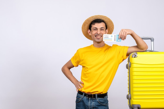 Вид спереди счастливый молодой турист, стоящий возле желтого чемодана, положив руку на талию, держа авиабилет