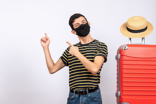 Front view happy young tourist with black mask standing near red suitcase pointing behind