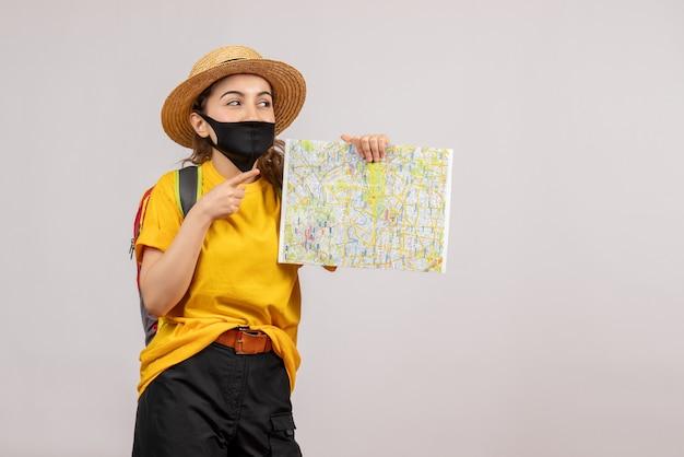 Vista frontale del giovane viaggiatore felice con lo zaino che sostiene la mappa sul muro grigio