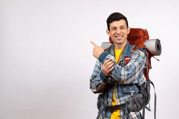 Front view happy young traveller with backpack pointing at behind