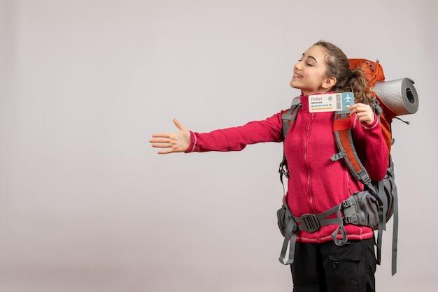 Vista frontale del giovane viaggiatore felice con il grande zaino che sostiene il biglietto di viaggio che dà la mano sulla parete grigia