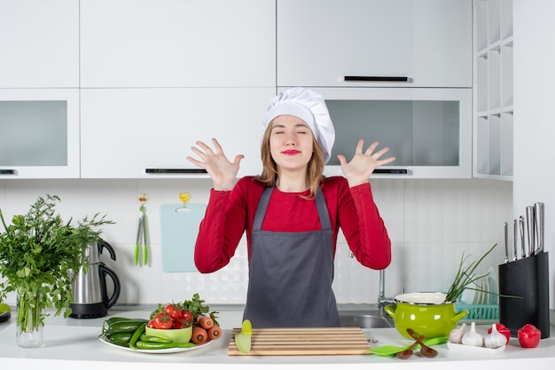 Front view happy young woman in apron with closed eyes raising hands