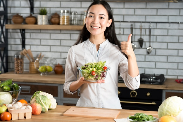Front view of happy young woman holding glass of bowl with salad showing thumb up sign in kitchen