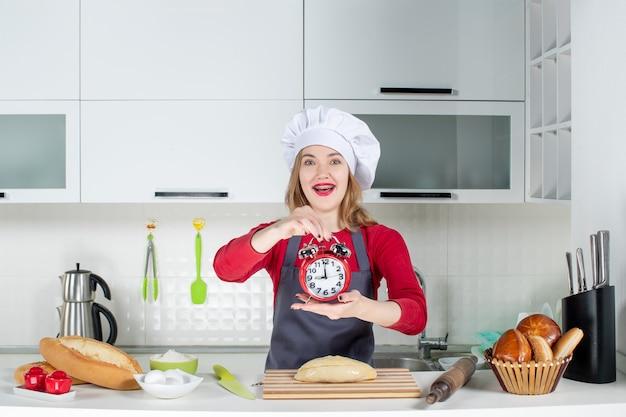 正面図キッチンで赤い目覚まし時計を保持している幸せな若い女性