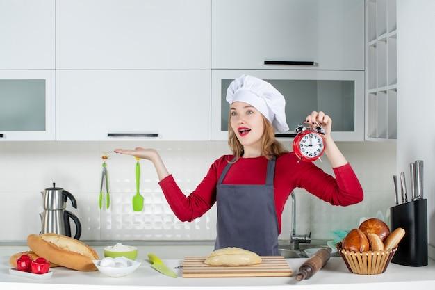 キッチンで赤い目覚まし時計を保持しているクック帽子とエプロンの正面図幸せな若い女性