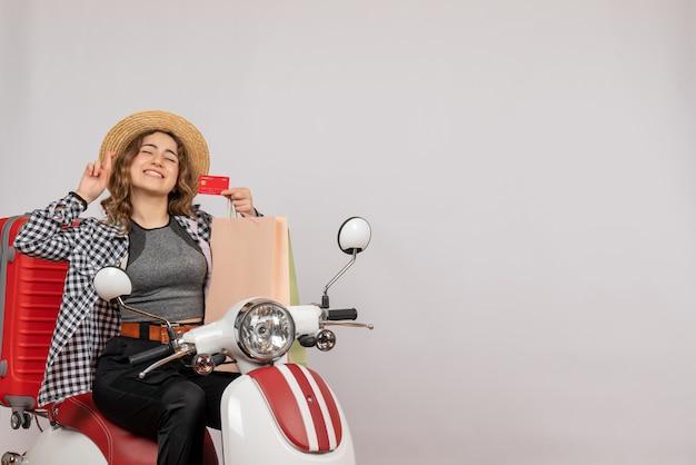 Vista frontale della giovane donna felice sulla scheda della holding del ciclomotore sul muro grigio