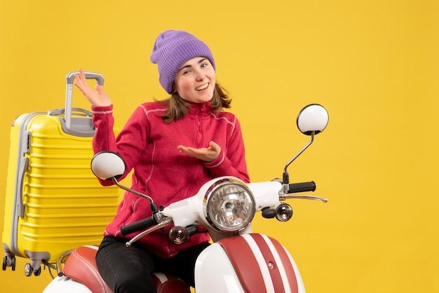 Giovane donna felice di vista frontale sul ciclomotore che indica qualcosa