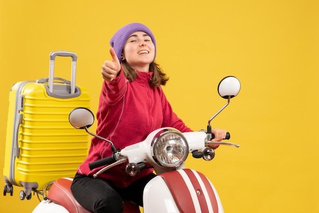 Вид спереди счастливая молодая женщина на мопеде, показывая пальцы вверх