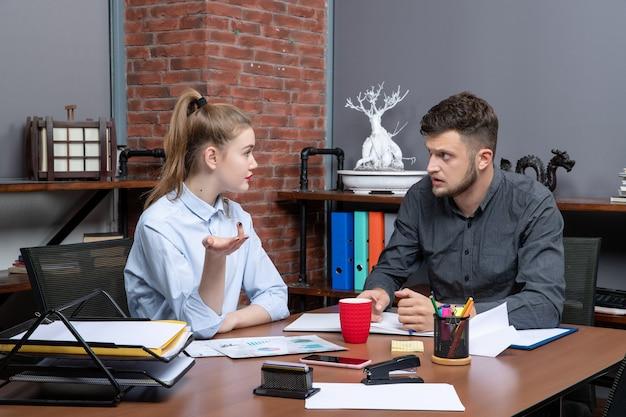 Vista frontale del team di professionisti laboriosi e fiduciosi che discutono di un problema nei documenti in ufficio
