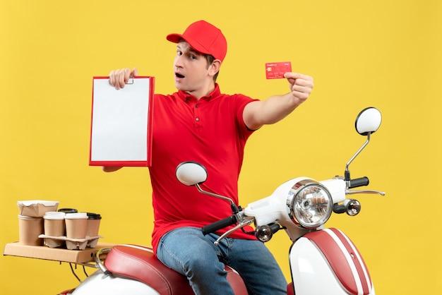 Vista frontale del giovane lavoratore laborioso che indossa camicetta rossa e carta di credito che consegna gli ordini che tengono documento e carta di credito su sfondo giallo