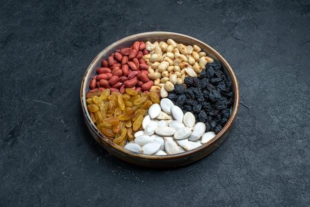 濃い灰色の表面にある正面図のヘーゼルナッツとレーズンおよびその他のナッツ