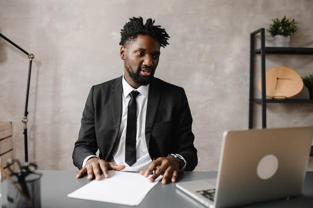 Вид спереди выстрел в голову молодой улыбающийся афро-американский бизнесмен, глядя на экран ноутбука