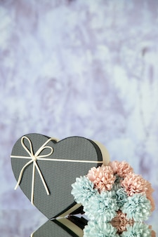 Front view of heart box colored flowers on grey abstract background with free space