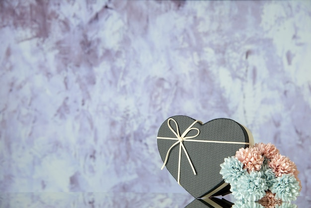 Front view of heart box with black cover colored flowers on grey abstract background with free space