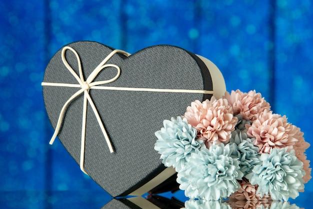 Scatola cuore vista frontale con fiori di copertura nera su sfondo blu spazio libero