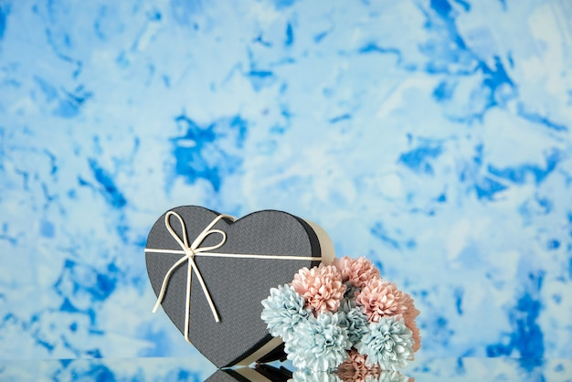 Front view of heart gift box with black cover colored flowers on blue blurred background
