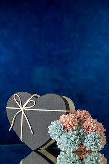 Front view of heart gift box with black cover colored flowers on dark background